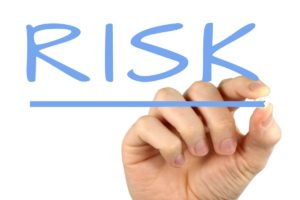 A hand writing the work 'risk' on your screen